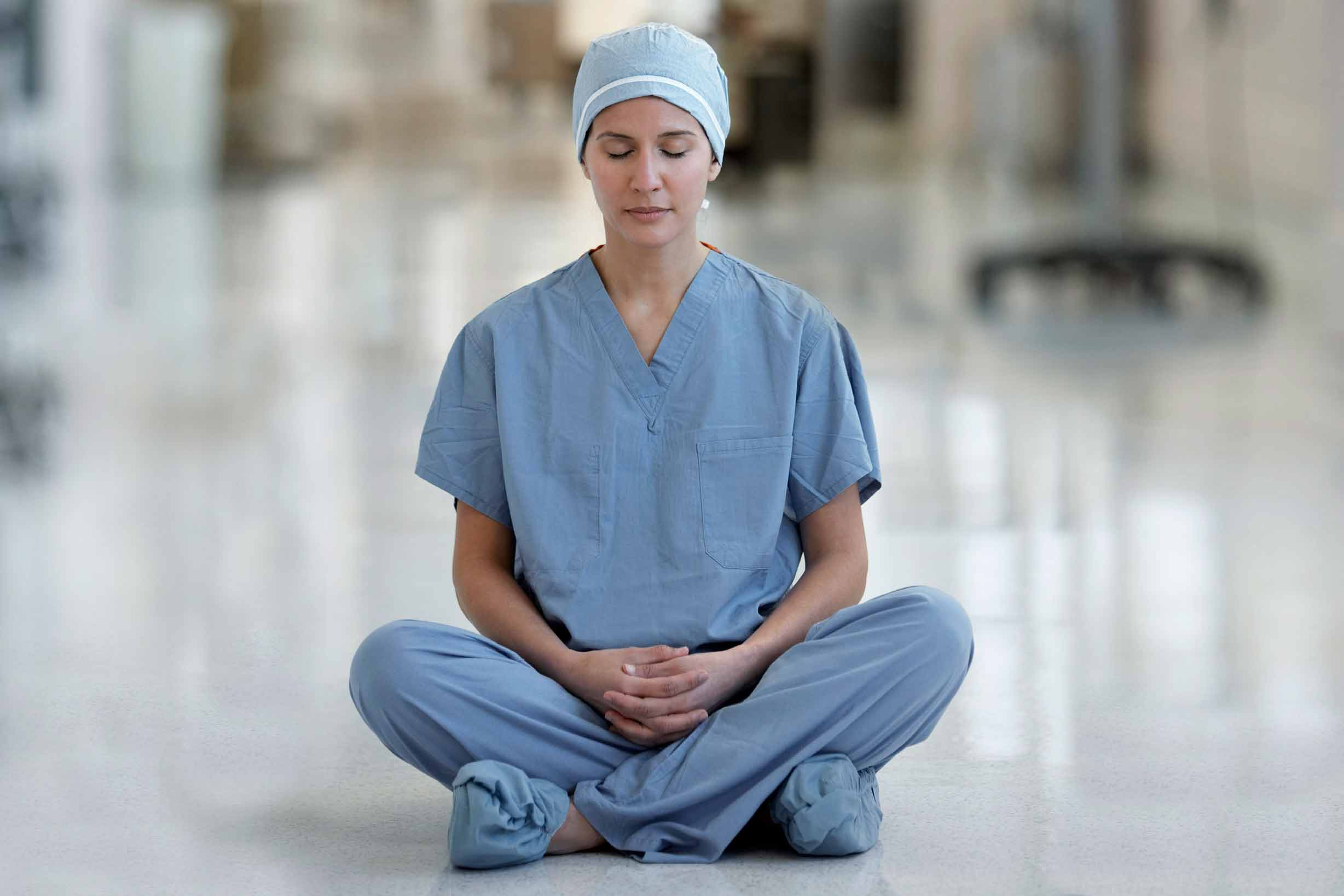 Nurse meditating in a hospital hallway